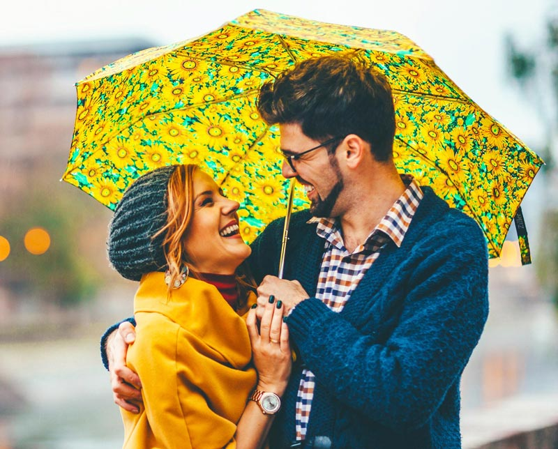 A couple under a yellow umbrella