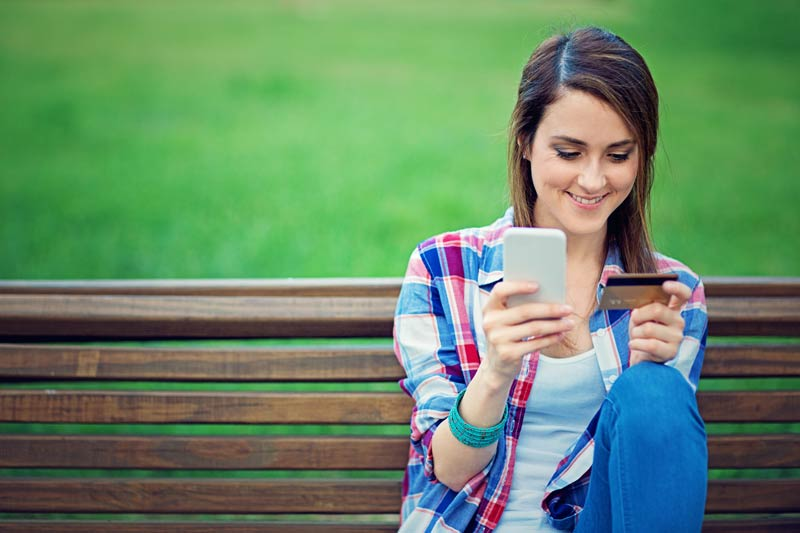 Girl in a plaid shirt sitting on a park bench with her phone
