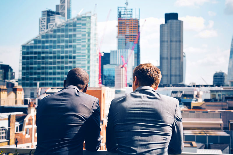 Two business men looking out over a large city